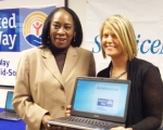 (From left) Loretta Hurt and Heather Wilson with one of the donated laptop computers
