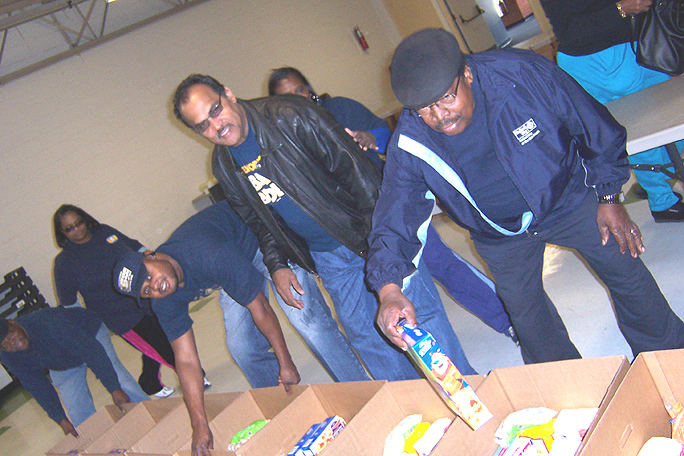 (From right) Casel Jones, Irvin Calliste and labor members assemble Christmas food boxes for people in need this year.